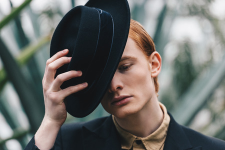 pensive handsome young red-haired man wearing black hat