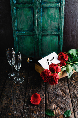 Love card, red roses and champagne bottle with glasses on shabby table, valentines day concept Stok Fotoğraf
