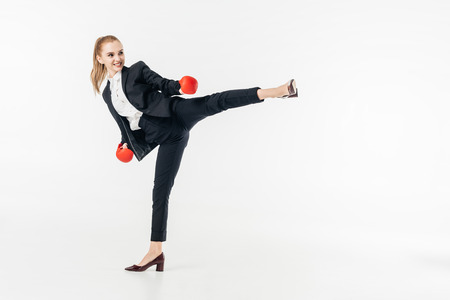businesswoman performing kick in suit isolated on white