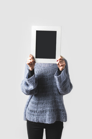 woman covering face with empty black board isolated on white