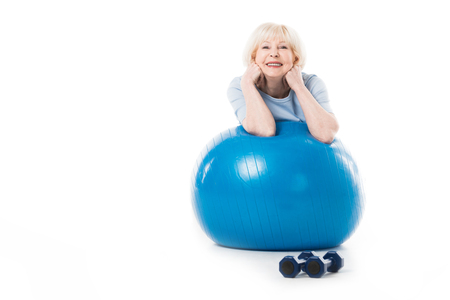 Smiling senior sportswoman with elbows on fitness ball and dumbbells on floor isolated on white Stock Photo
