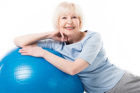 Portrait of smiling senior sportswoman with fitness ball isolated on white Stock Photo