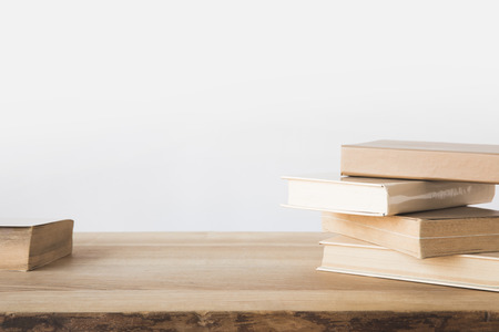 stack of old books on wooden table on white Stock Photo
