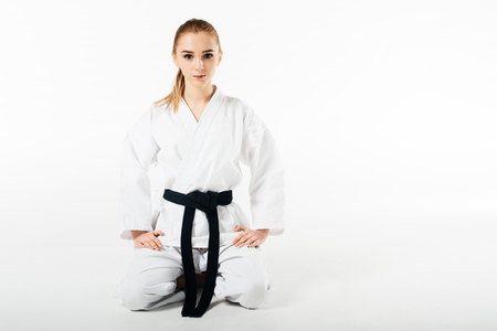 female karate fighter sitting and looking at camera isolated on white Imagens