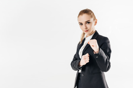 female karate fighter standing in suit and showing fists isolated on white Imagens
