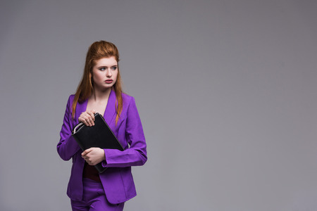 Young female fashion model in purple suit holding handbag isolated on grey