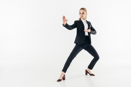businesswoman in suit standing in karate position and looking away isolated on white 免版税图像