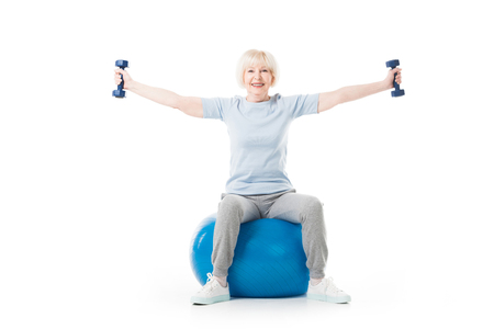 Senior sportswoman with dumbbells in wide hands sitting on fitness ball isolated on white