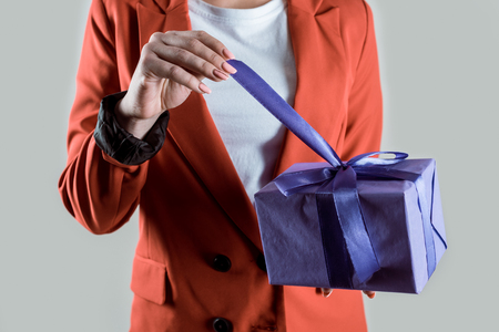 Close-up view of woman opening gift box isolated on grey