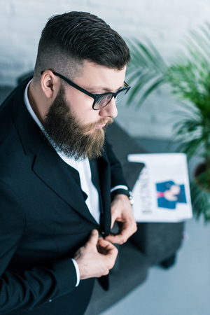 high angle view of stylish businessman in eyeglasses buttoning jacket