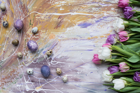 Painted chicken and quail eggs and tulips on stained background 스톡 콘텐츠