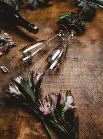 flowers, champagne bottle and glasses on wooden table