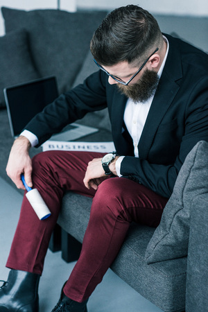 businessman cleaning pants with sticky brush while sitting on sofa