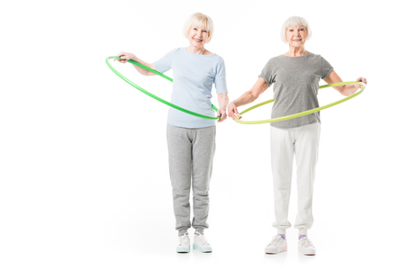 Two senior sportswomen doing hula hoop excercise isolated on white Stock Photo