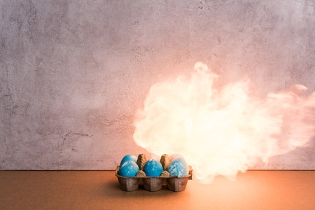 Painted eggs on fire on grey background 스톡 콘텐츠