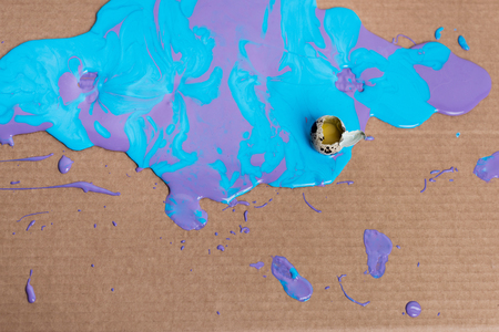 Broken quail egg in paint on cardboard background Stockfoto