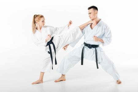 Combattant de karaté féminin coups de pied partenaire masculin isolated on white