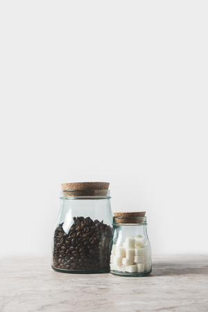 coffee beans and refined sugar in glass bottles on marble table on white