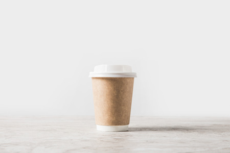one disposable coffee cup on marble table on white 스톡 콘텐츠