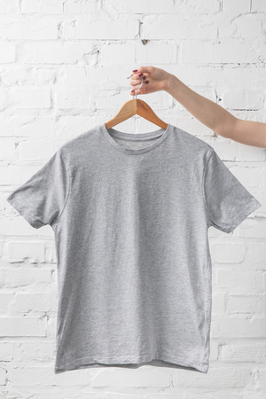 cropped image of woman holding grey shirt on hanger