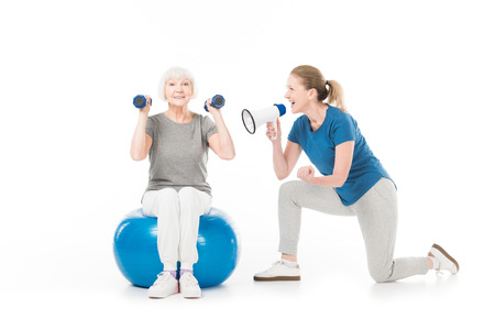 Coach with megaphone and sportswoman with dumbbells and fitness ball isolated on white Stock Photo