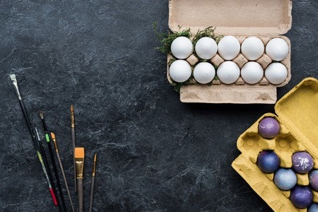 Painted and white chicken eggs in cartons on dark background Stock Photo