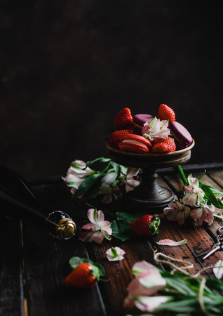 bowl with macarons and strawberries on wooden table with flowers and champagne bottle for valentines day Stok Fotoğraf - 111818500