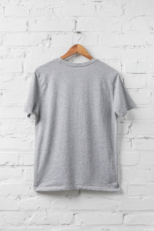 one grey shirt on hanger on white wall