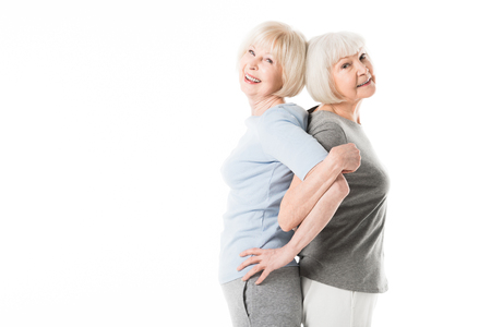 Two senior sportswomen standing back to back while doing excercise isolated on white Stock Photo