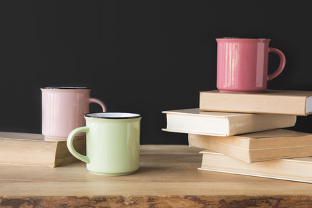 three colored cups and books on wooden table on black