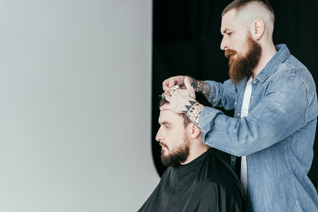 side view of barber cutting customer hair at barbershop