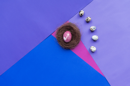 flat lay with quail eggs around chicken egg in nest on background in purple tones Zdjęcie Seryjne