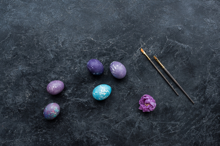 Painted eggs with brushes on dark background Stock Photo