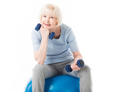 Senior sportswoman sitting on fitness ball with dumbbells in hands isolated on white