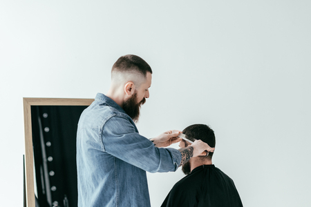 barber cutting customer hair at barbershop isolated on white