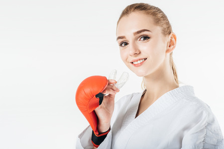 smiling female karate fighter holding mouthguard isolated on white Stock Photo