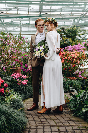 full length view of beautiful young elegant wedding couple standing together between flowers in botanical garden 写真素材