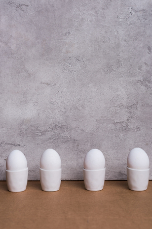 Row of white eggs in cups on grey background