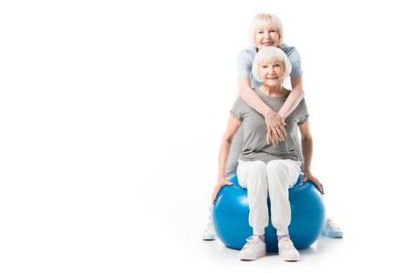 Smiling senior sportswomen with fitness ball isolated on white