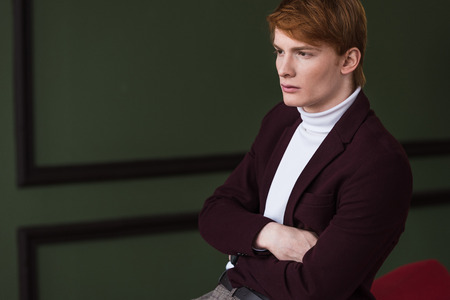 Side view of male model in jacket sitting on couch