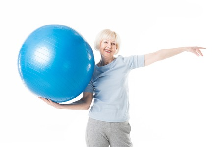 Smiling senior sportswoman holding fitness ball in one hand isolated on white