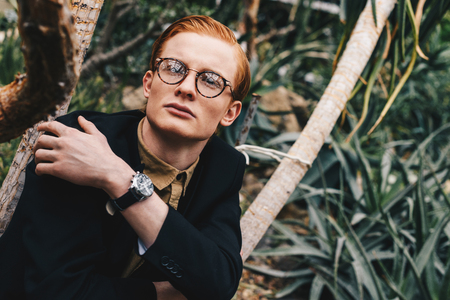 pensive stylish young redhead man in eyeglasses looking away in botanical garden