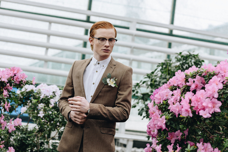 handsome stylish young redhead groom in eyeglasses looking away in botanical garden
