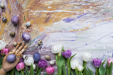 Painted eggs with mannequin hand and tulips on stained background Stockfoto