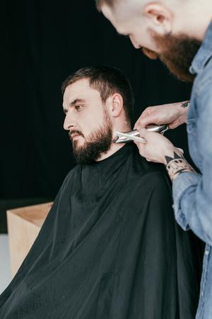 barber trimming customer beard at barbershop