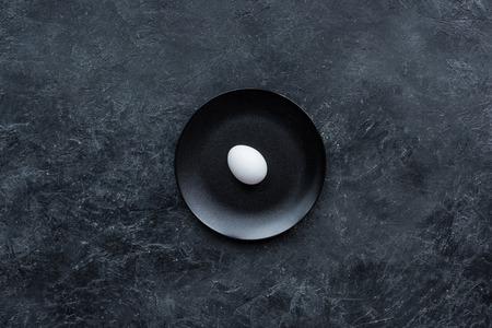 White egg on black plate on dark background