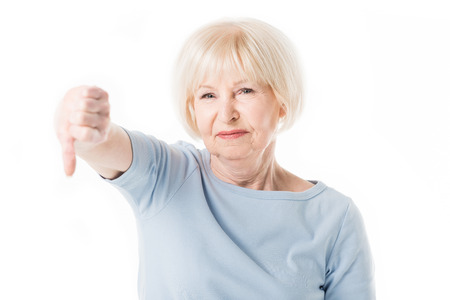 Senior woman with thumb down gesture isolated on white