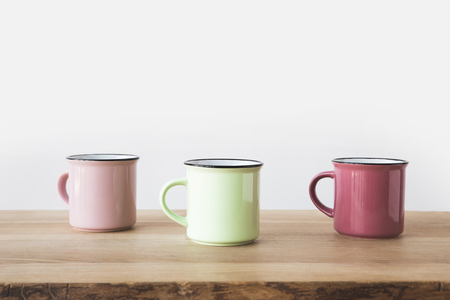 three colored cups on wooden table on white Stock Photo