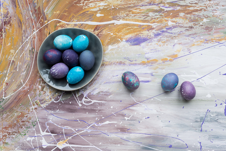 Painted chicken eggs in bowl and on stained background