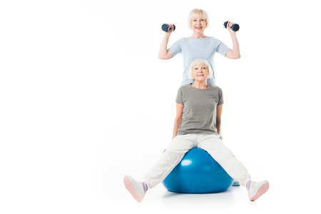 Two senior sportswomen with fitness ball and dumbbells isolated on white